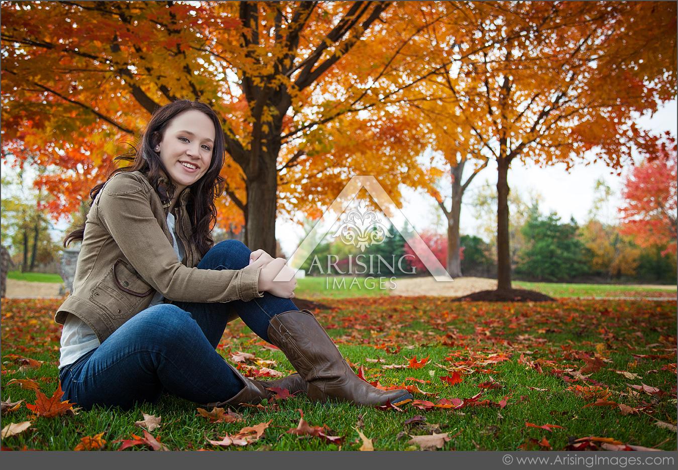 senior smiling next to a michigan fall tree