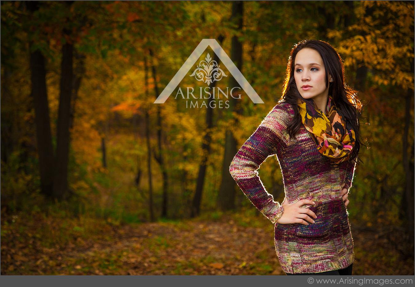 senior girl posing in michigan fall colored woods